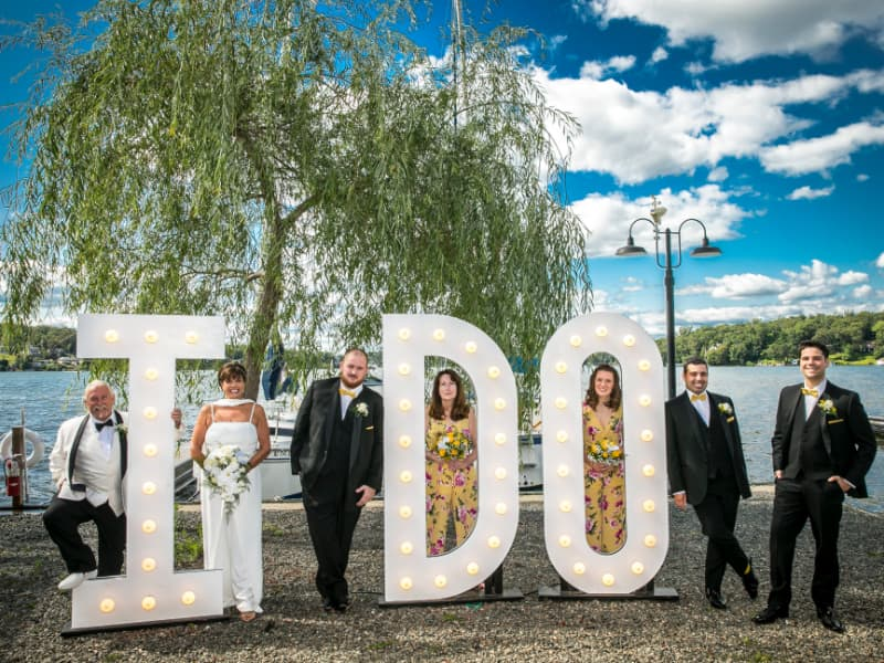 Newlyweds and wedding party by I Do letters.