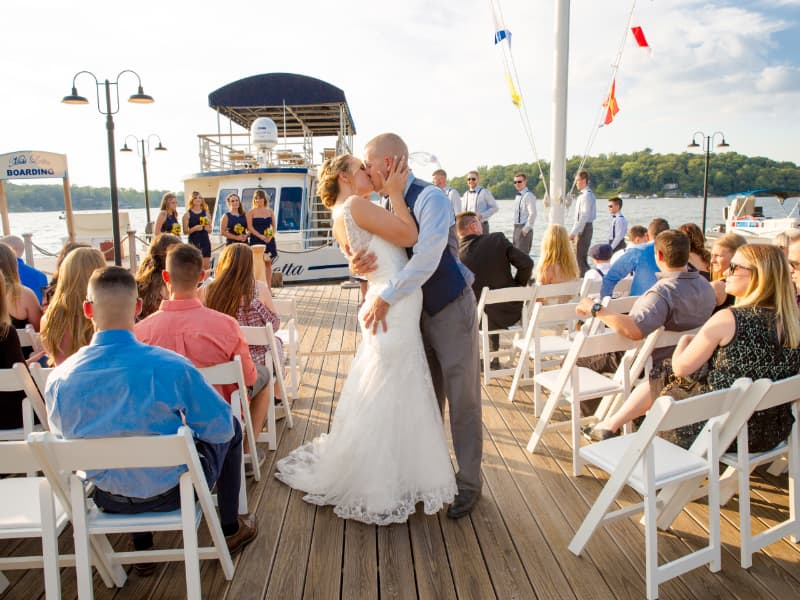 Man and woman kissing on the dock, surrounded by guests