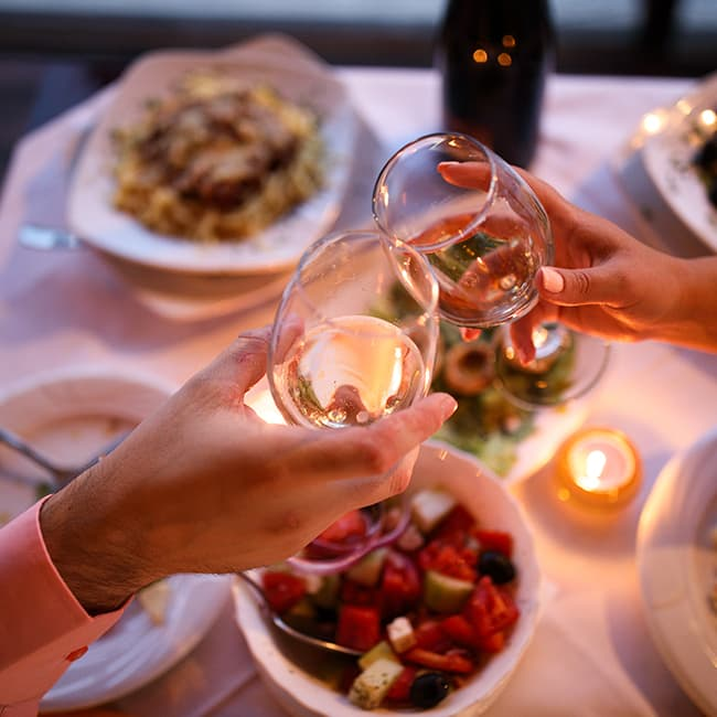 Two adults touching wine glasses over a spread of food in a romantic setting