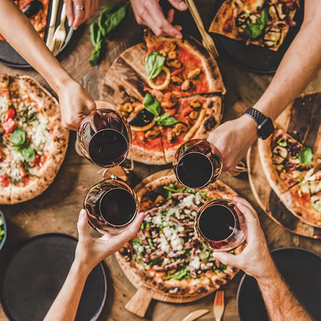 Four people touching wine glasses over a dinner table with pizza